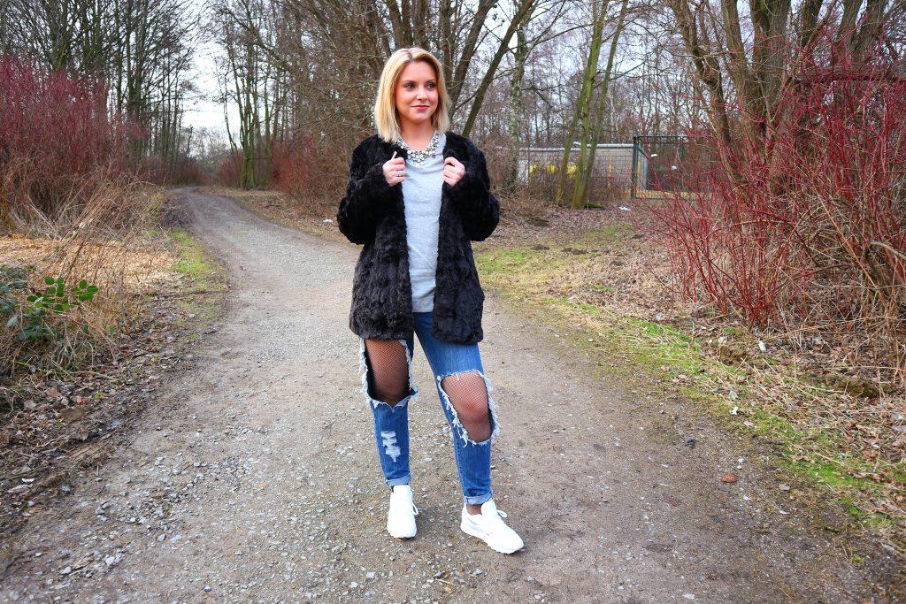 Ein Outfit mit zerrissenen Jeans und Netzstrumpfhosen